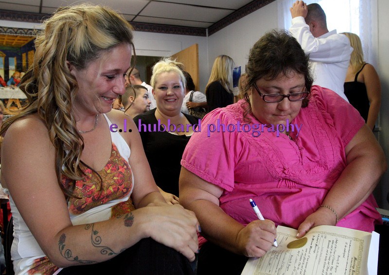 E.L. Hubbard photography<br /> Michelle Rose, the mother of the groom, watches as Christine Quimby, the mother of the bride, signs the marriage license for Kari Gregory and Nathan Carberry before their wedding at New Life Ministries in Hamilton Tuesday, Aug. 16, 2011.