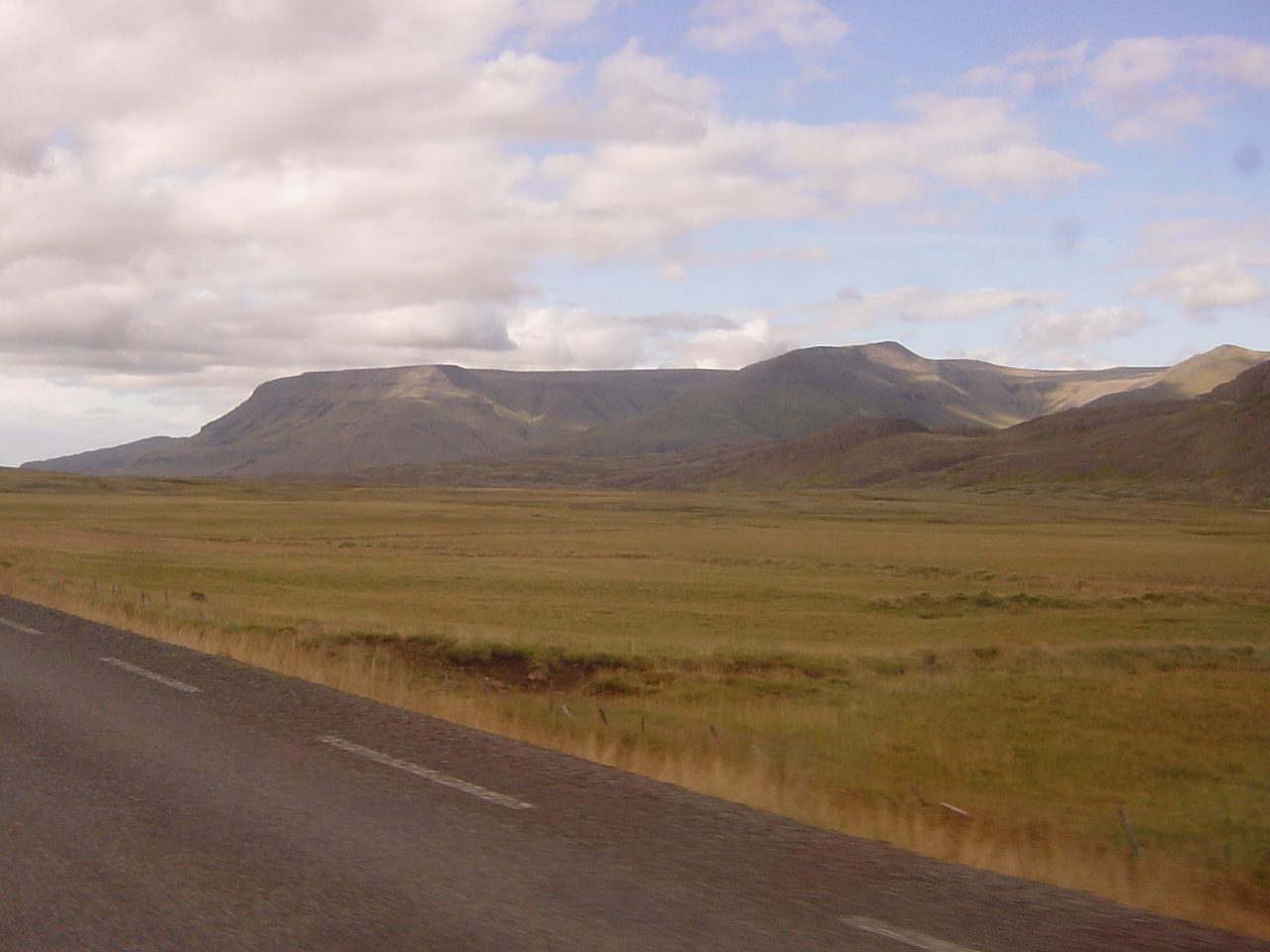 Views from our bus tour. This is tipical Icelandic landscape: flat rocks with a bit of grass or moss. There are harly any bushes or trees (unless imported). In the back the mountains (up to 2400m high!) with glaciers.
