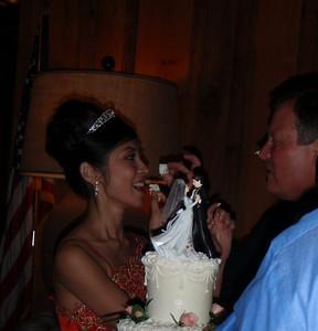Hong and Craig sharing wedding cake and icing on Craig's nose
