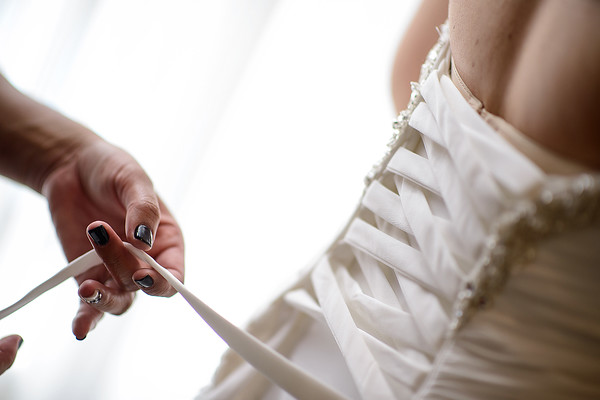 bride putting a corset wedding dress