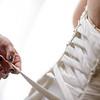 bride putting a corset wedding dress