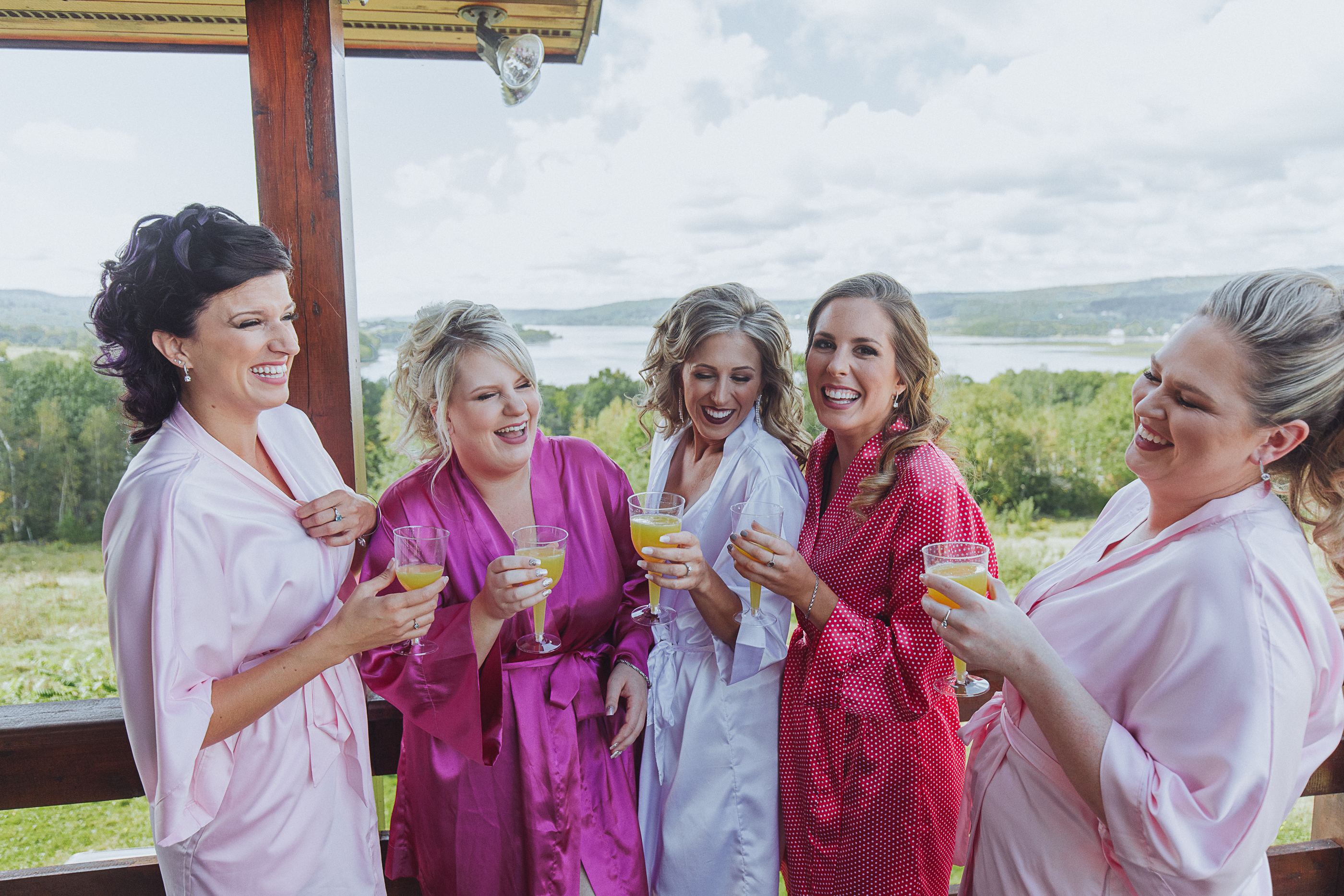 girls laughing over drinks - wedding morning
