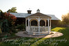 Gazebo in middle of grassy area.  Wedding cake will be in gazebo.  Behind gazebo is hall, dancing will be in hall.
