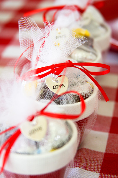 Chocolate candies in a tiny pot wrapped in lace with a ribbon and a love trinket