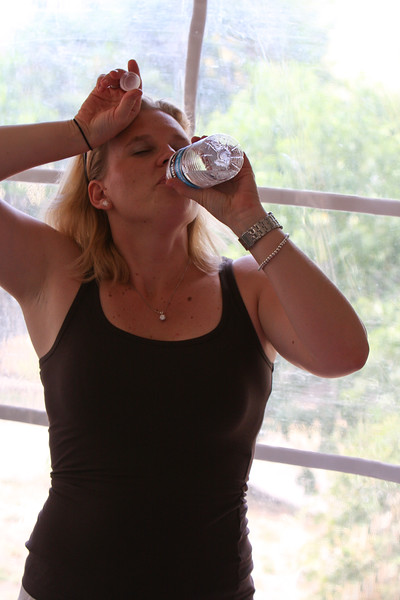 Stephanie drinks bottled water to survive the 100 degree heat