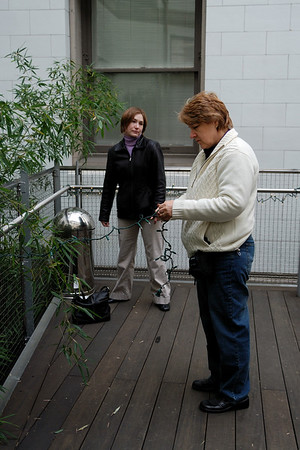The first thing we did to get ready at the library was to string small white lights on the railing around the deck.  The ceremony was held in front of large glass doors that lead out to the deck, so this was the background for the ceremony.  Cindy's mom and sister are helping.