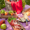 Picnic at the park on the grass: tablecloth, basket, healthy food, rose wine and accessories