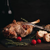 Freshly roasted lamb leg with herbs and bottle of red wine