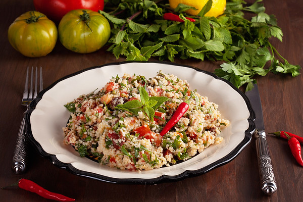 Tabbouleh - Middle Eastern vegetarian dish with couscous, tomatoes, parsley, dried raisins and mintseasoned with olive oil and lemon juice. Easy authentic recipe
