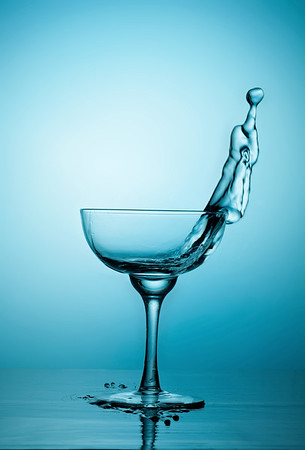 Water or alcohol splashes out of a glass