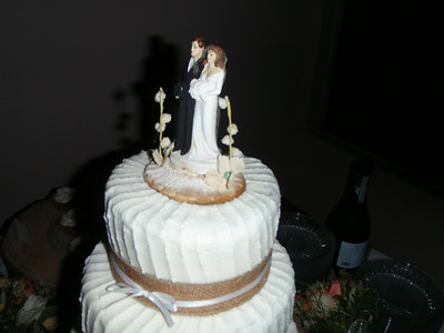 The wedding cake topper was previously used by the groom's grandparents.  Burlap bands encircled each cake layer.