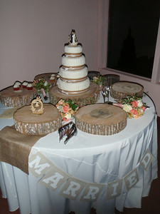 "The wedding cake table was adorned with ""log platters"" that held a variety of cupcakes (lemon, red velvet, vanilla, chocolate, carrot) for dessert prior to cutting the cake.  The cupcake platters were restocked throughout the evening."