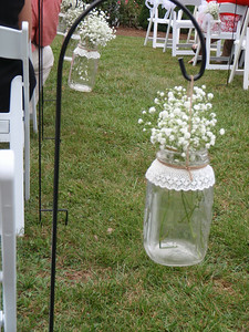 Babies breath flowers in mason jars hung on shepherd hooks adorned each row of seats at the outdoor ceremony.
