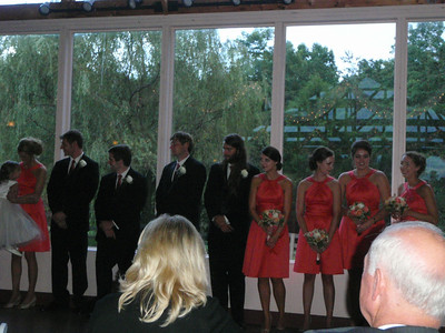 Bridesmaids in coral satin dresses stand with the groomsmen.