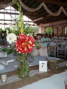Table decorations included 1/2 gallon Mason jars with gorgeous flowers on a burlap and lace runner with votive candles.