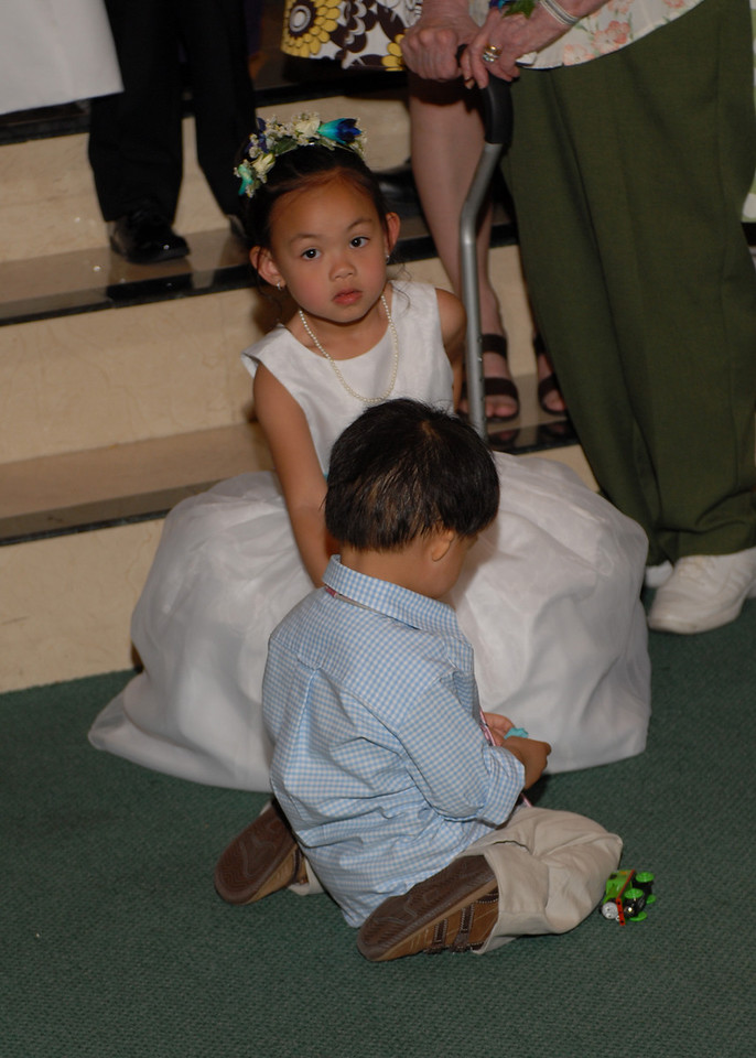 The flower girl waits while everyone gets into position for a family photo.