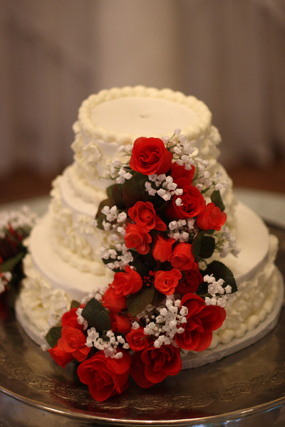 The wedding cake was adorned with red flowers.