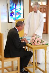 John signing the register.