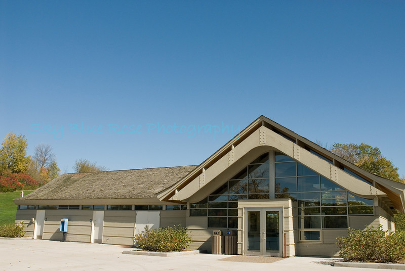 Fish Lake Regional Park Pavilion. This is the front of the pavilion which has a large patio (cement area you see) and at least one picnic table. Beyond that area is a beach with a beautiful scenic area in the background. On the left side of the picture there is a grassy area, more tables, and a volleyball net.