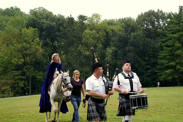 The bride approaches, wearing a blue cape and atop a white horse, her arrival heralded by the bagpiper and drummer.