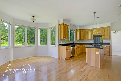 Spacious kitchen room with polished hardwood floor.