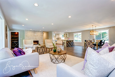 Spacious white living area with stone fireplace