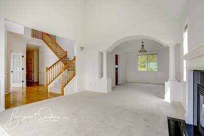 Empty formal dining room with white walls.