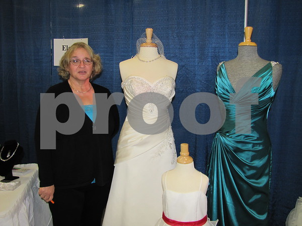 Elaine Echelberger, owner of Elaine's Bridal stands next to some of the gowns they offer.