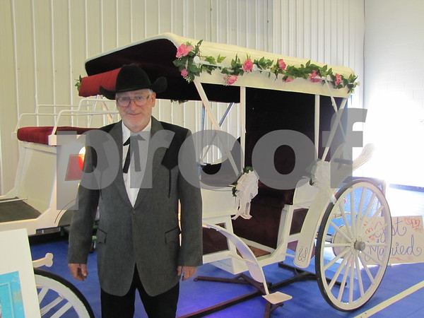 Jim Kellner, owner of Dream Carriage Rides, stands before the wedding carriage he had on display at The Messenger's Bridal Show in the Career Ed building on the ICCC campus.