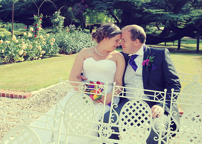 A bride and groom in the gardens at Spains Hall photographed at their summer wedding