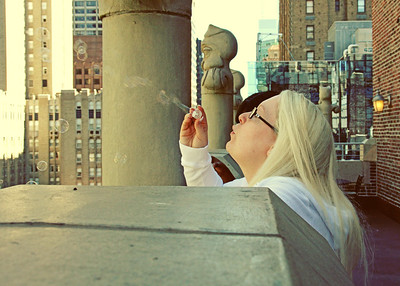 A bride and her bridal party blowing bubbles out over the new york skyline on a wedding day