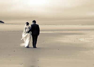 A bride and groom at Sea Palling Beach for photographs on their wedding day following their wedding ceremony at Dairy Barns