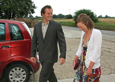 A groom greeting guests arriving at a wedding at Dairy Barns