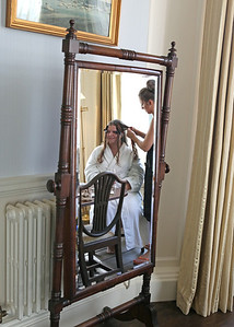 A bride getting ready in the Tapestry Room at Spains Hall on her wedding day