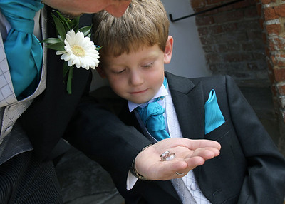 A pageboy looking at the rings before a wedding ceremony in the Elizabethan Hall at Spains Hall