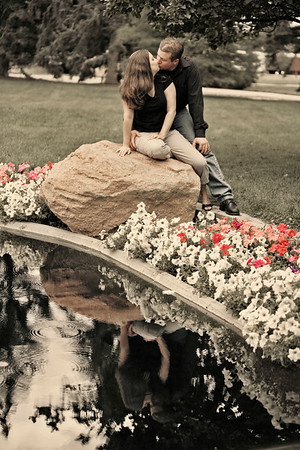 Krista and Scott share a kiss during their engagement portrait session held at a Denver University garden.