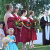 photographer getting stared at by kid during the ceremony, bridesmaids and priest  behind her.