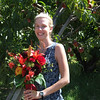 Bride with beautiful flowers poses for portrait in front of a peach tree.