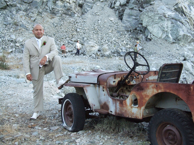 Portrait of the best man at site of a rusted jeep from another era.