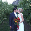 Bride and groom, with flowers and kissing in apple orchid near Wenatchee,WA. Photography by Nick Shiflet