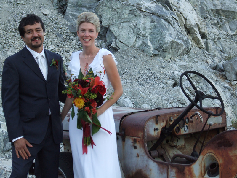 portrait of bride and groom with historical jeep owned by family members.