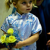 The flower girl, dressed in a traditional Chinese qipao, gets encouraged to walk down the aisle from her dad.