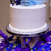 The wedding cake is decorated with edible flowers and a bow.