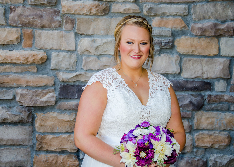 Riess wedding bride in front of brick