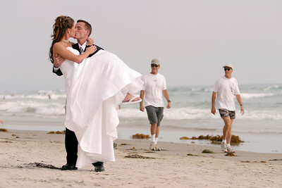 Jeff plants one on his new bride while carrying her back up the beach.