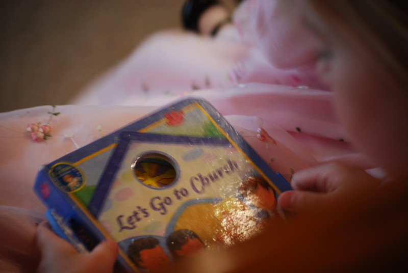 "Photo of child reading, ""Let's Go to Church"" during ceremony of her grandparents in Pewaukee."