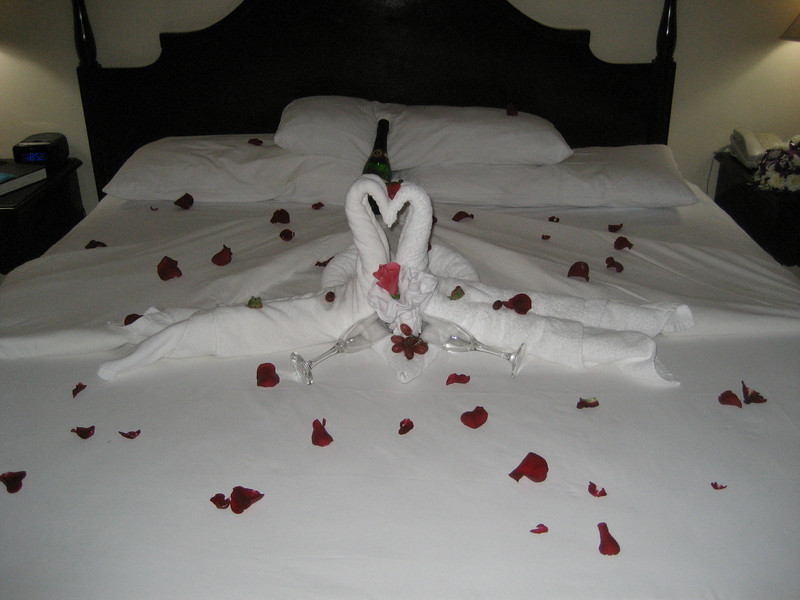 The bed in our room decorated for our wedding night.  Also pictured is one of the many bottles of champagne the resort kept giving us.  (We might have drunk half of one bottle.)