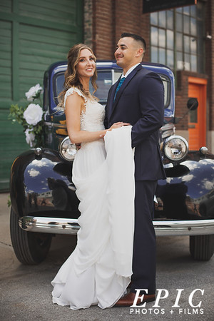 Bride and groom in front of classic car in kansas city