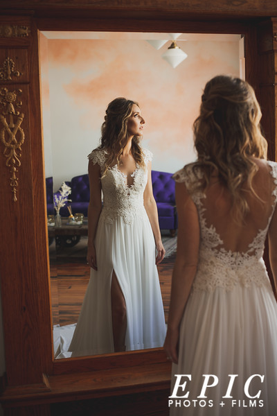 Bride in her wedding dress in front of a mirror