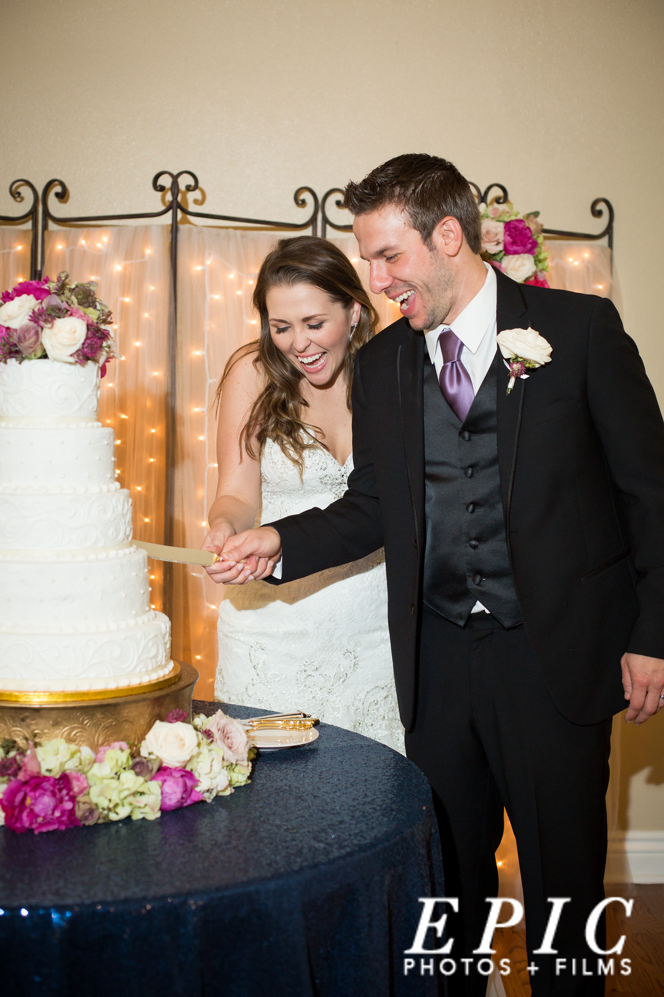 bride and groom smiling as they cut their wedding cake